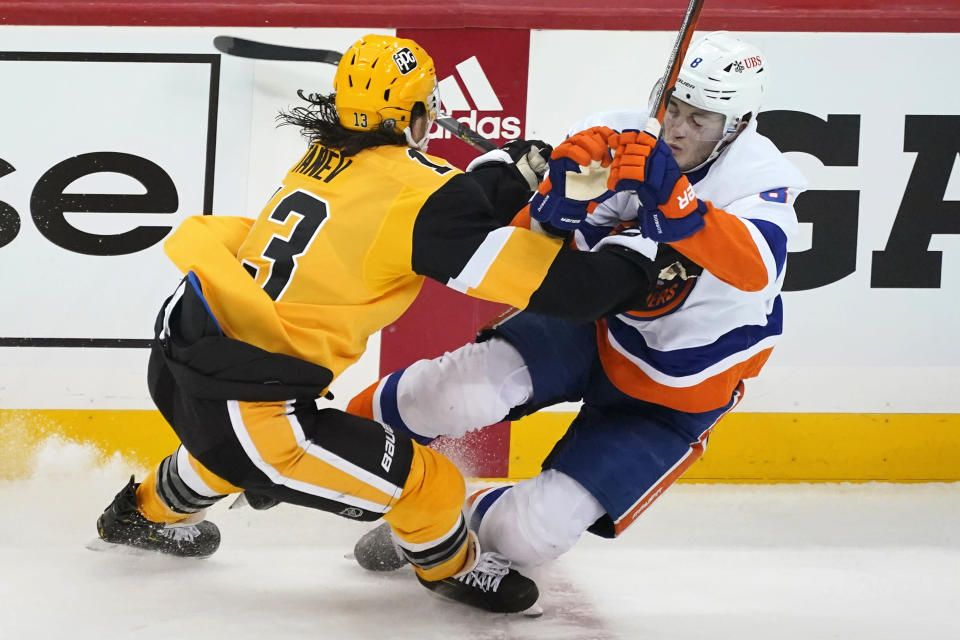 Pittsburgh Penguins' Brandon Tanev, left, checks New York Islanders' Noah Dobson off his skates during the first period in Game 1 of an NHL hockey Stanley Cup first-round playoff series in Pittsburgh, Sunday, May 16, 2021. (AP Photo/Gene J. Puskar)