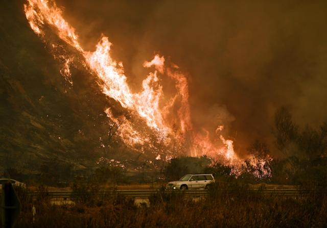 <p>Vehicles pass beside a wall of flames on the 101 highway as it reaches the coast during the Thomas wildfire near Ventura, California on Dec. 6, 2017. (Photo: Mark Ralston/AFP/Getty Images) </p>
