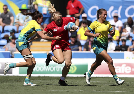 Canada's Sara Kaljuvee, centre, attempts to run past Australian defenders during their rugby sevens semifinal at Robina Stadium during the 2018 Commonwealth Games on the Gold Coast, Australia, Sunday, April 15, 2018. (AP Photo/Rick Rycroft)