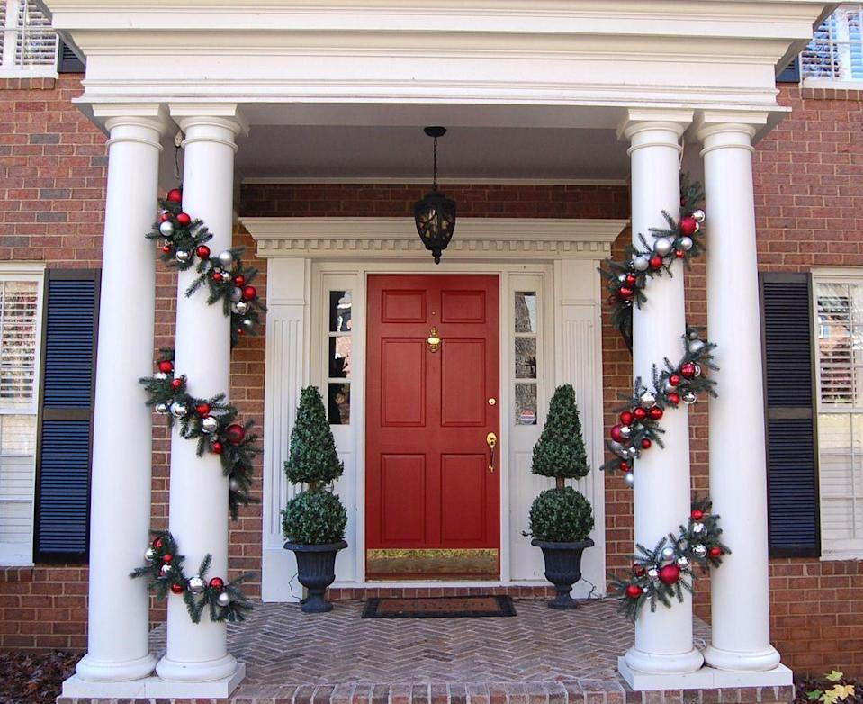 "<p>The Christmas presents shouldn't get all the attention. Wrap up your home, too—in garland. This decor from <a href=""http://betweennapsontheporch.net/christmas-porch-decorating-ideas/"" rel=""nofollow noopener"" target=""_blank"" data-ylk=""slk:Between Naps On The Porch"" class=""link rapid-noclick-resp"">Between Naps On The Porch</a> features ornament-speckled garland twisted around the home's columns. Simply picturesque. </p>"