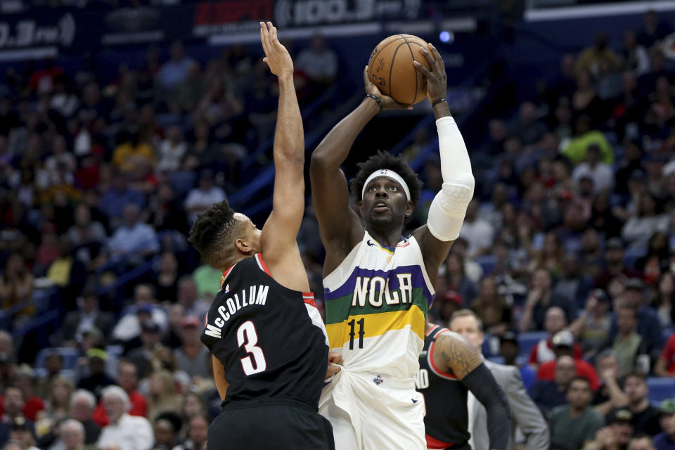 FILE - In this Feb. 11, 2020, file photo, New Orleans Pelicans guard Jrue Holiday (11) shoots a basket as Portland Trail Blazers guard CJ McCollum (3) defends in the second half of an NBA basketball game in New Orleans. Jrue Holiday is being traded from New Orleans to Milwaukee, which is aiming to give two-time reigning NBA MVP Giannis Antetokounmpo the improved roster that he seeks with the decision on his supermax contract extension looming, a person with knowledge of the situation said Tuesday, Nov. 17, 2020. The Pelicans are getting Eric Bledsoe, George Hill and a package of future first-round draft picks from the Bucks, the person told The Associated Press. The person spoke on condition of anonymity because no deal had been finalized. (AP Photo/Rusty Costanza, File)