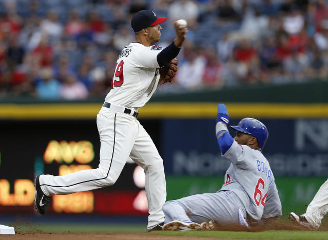 Atlanta Braves shortstop Andrelton Simmons (19) avoids Chicago Cubs' Emilio Bonifacio (64) as he turns a double play on a Ryan Kalish (51) ground ball in the first inning of a baseball game on Saturday, May 10, 2014, in Atlanta. (AP Photo/John Bazemore)