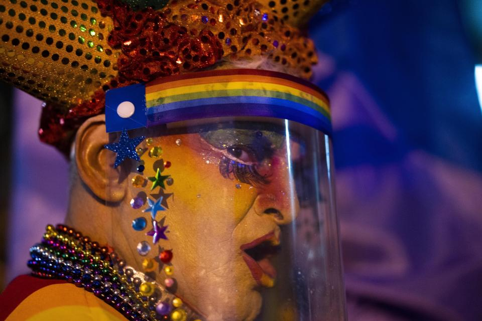 A person wearing a face mask amid of new coronavirus pandemic dances during the Diversity parade in Montevideo, Uruguay, Friday, Sept. 25, 2020. The event is held every year to raise awareness and fight against discrimination based on sexual identity and orientation. (AP Photo/Matilde Campodonico)