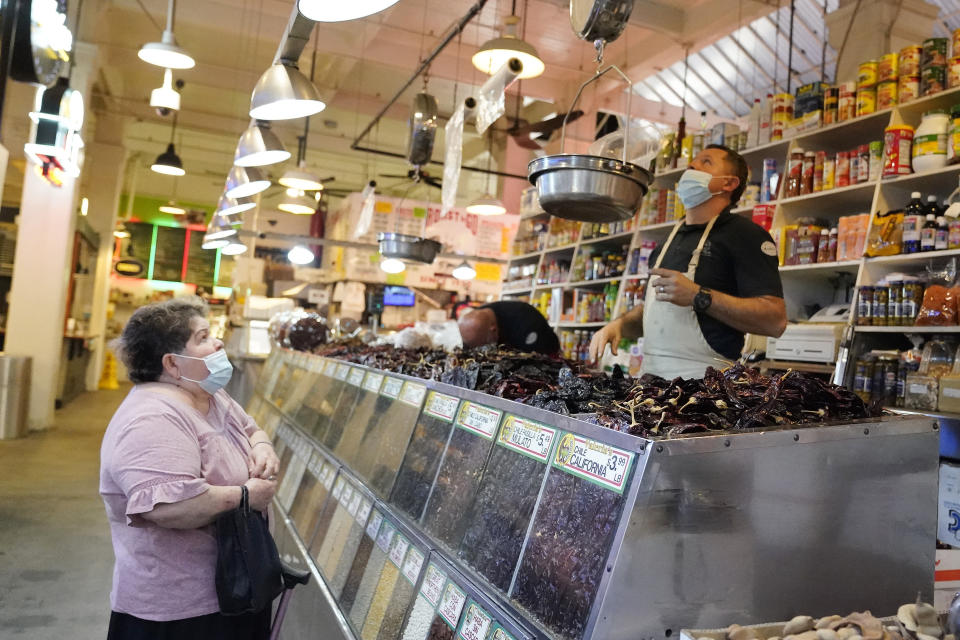 A customer, at left, is tended to at the Grand Central Market Monday, Nov. 16, 2020, in Los Angeles. California Gov. Gavin Newsom announced Monday, Nov. 16, 2020, that due to the rise of COVID-19 cases, Some counties have been moved to the state's most restrictive set of rules. The new rules begin, Tuesday, Nov. 17. (AP Photo/Marcio Jose Sanchez)