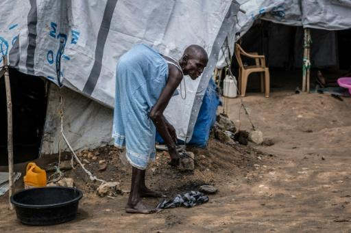 Kot Lero, who has spinal tuberculosis, cleans around her shelter. The camp houses around 7,000 people who have fled South Sudan's conflict -- 200 of them have severe disabilities