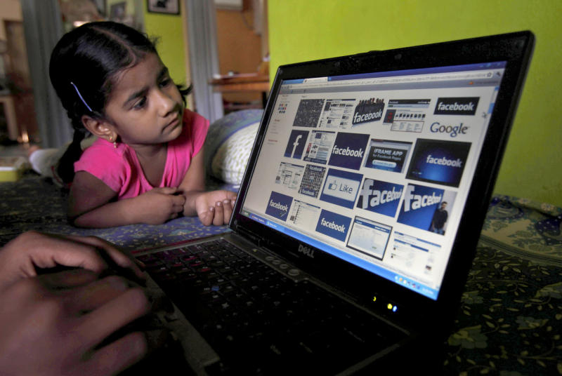 FILE- In this Friday, May 18, 2012, file photo, a child  looks at a laptop displaying Facebook logos in Hyderabad, India. Facebook said Monday, June 4, 2012, it is testing out ways to allow younger kids on its site without needing to lie. (AP Photo/Mahesh Kumar A., File)