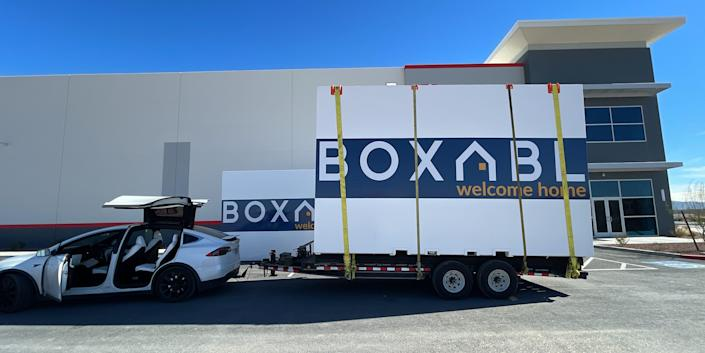 boxabl logo on moving containers being pulled by Tesla