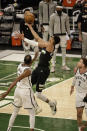 Milwaukee Bucks forward Giannis Antetokounmpo, center, shoots against Brooklyn Nets' Kevin Durant, left, during the second half of Game 6 of a second-round NBA basketball playoff series Thursday, June 17, 2021, in Milwaukee. (AP Photo/Jeffrey Phelps)