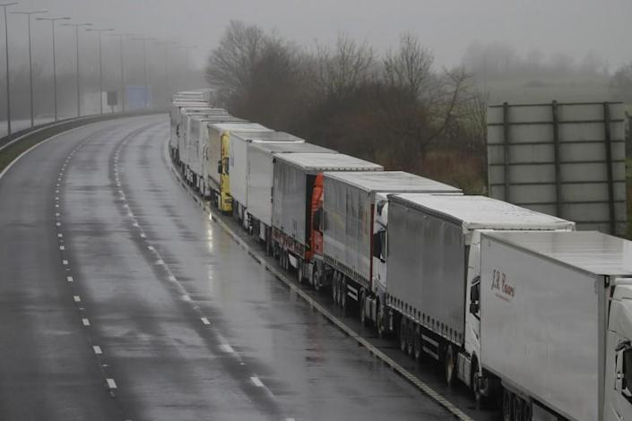 Lorries parked on the M20 near Folkestone, England, Monday, Dec. 21, 2020, as part of Operation Stack after the Port of Dover was closed and access to the Eurotunnel terminal suspended following the French government's announcement. France banned all travel from the UK for 48 hours from midnight Sunday, including trucks carrying freight through the tunnel under the English Channel or from the port of Dover on England's south coast. (AP Photo/Kirsty Wigglesworth)