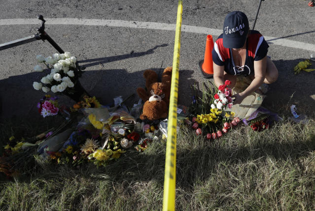 <p>Rebecca Thompson places flowers at a makeshift memorial near the scene of a shooting at the First Baptist Church of Sutherland Springs to honor victims, Monday, Nov. 6, 2017, in Sutherland Springs, Texas. (Photo: Eric Gay/AP) </p>