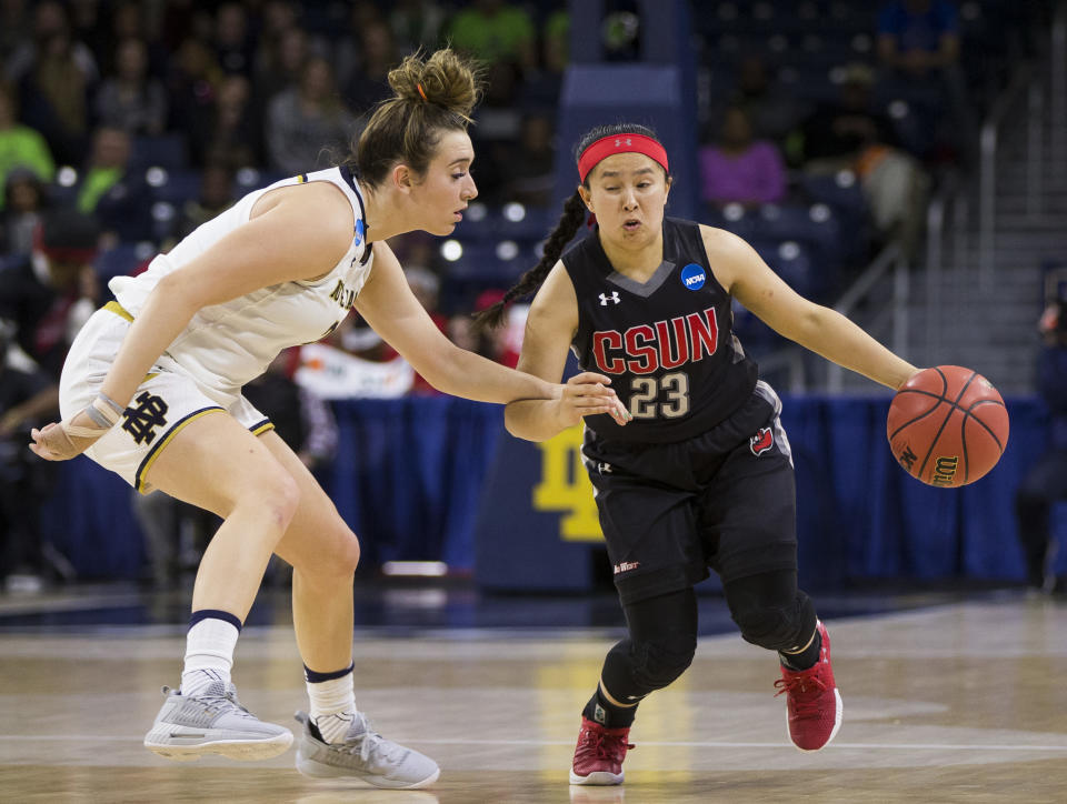 Cal State Northridge's HayleyTanabe (23) drives in against Notre Dame's Marina Mabrey during a first-round game in the NCAA women's college basketball tournament Friday, March 16, 2018, in South Bend, Ind. (AP Photo/Robert Franklin)