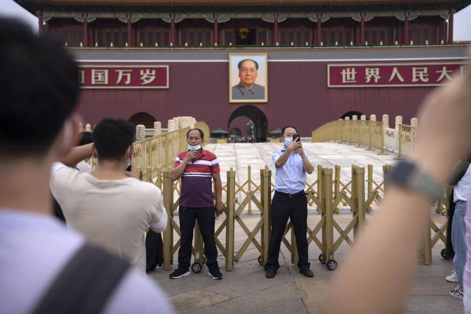 """Visitors wearing face masks pose for photos near a large portrait of Chinese leader Mao Zedong on Tiananmen Gate near Tiananmen Square in Beijing, Saturday, Sept. 18, 2021. China's """"zero tolerance"""" strategy of trying to isolate every case and stop transmission of the coronavirus has kept kept the country where the virus first was detected in late 2019 largely free of the disease. (AP Photo/Mark Schiefelbein)"""