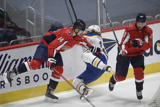 Washington Capitals right wing Richard Panik (14) checks Buffalo Sabres center Eric Staal (12) during the first period of an NHL hockey game, Sunday, Jan. 24, 2021, in Washington. Capitals center Lars Eller (20) looks on. (AP Photo/Nick Wass)