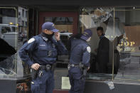 Police officers talk to a man through a broken window of Goorin Bros. Hat Shop in San Francisco, Sunday, May 31, 2020, after protests over the Memorial Day death of George Floyd. Floyd was a black man who was killed in police custody in Minneapolis on May 25. (AP Photo/Jeff Chiu)