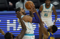 Charlotte Hornets forward P.J. Washington, center, shoots between Golden State Warriors forward Eric Paschall, bottom left, and forward Andrew Wiggins during the first half of an NBA basketball game in San Francisco, Friday, Feb. 26, 2021. (AP Photo/Jeff Chiu)