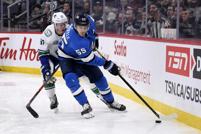 Winnipeg Jets' Mark Scheifele (55) carries the puck past Vancouver Canucks' Tyler Myers (57) during the second period of an NHL hockey game Tuesday, Jan. 14, 2020, in Winnipeg, Manitoba. (Fred Greenslade/The Canadian Press via AP)