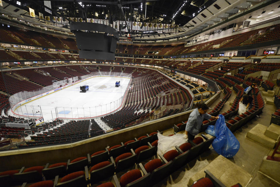 Workers clean up after an NHL hockey game between the Chicago Blackhawks and the San Jose Sharks at The United Center Wednesday, March 11, 2020, in Chicago. (AP Photo/Paul Beaty)