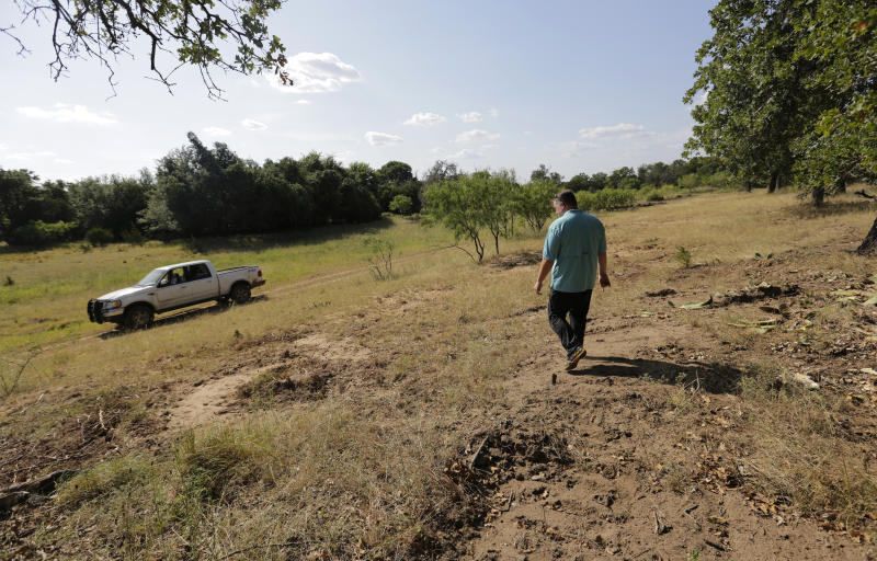 Heath Frantzen walk on his property near the site of a proposed new natural gas pipeline that would run through his ranch in the Texas Hill Country, where more than 600 white-tailed and trophy axis deer graze on a 260-acres his family has owned for three generations, near Fredericksburg, Texas Friday, Aug. 2, 2019. (AP Photo/Eric Gay)