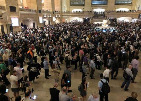 Commuters wait as service was temporarily suspended on all Metro North lines at Grand Central Terminal due to storms in Manhattan, New York