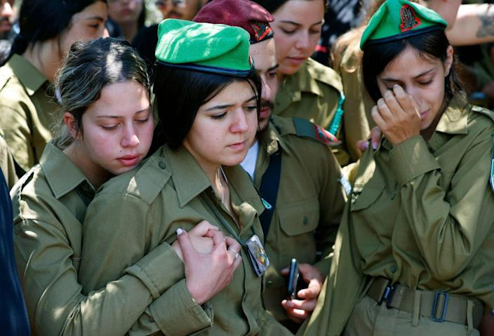 Israeli women in military uniforms embrace and weep