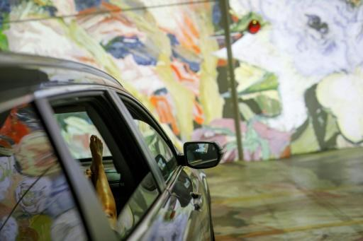 People sit in their cars as they experience a drive-in immersive Vincent Van Gogh art exhibit in Toronto, Ontario, Canada, on July 3, 2020. Amid the coronavirus pandemic, many events are having to rethink their programming and innovate in order to comply with social distancing measures