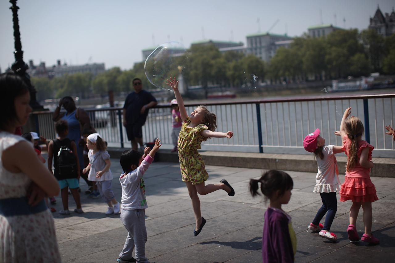 LONDON, UNITED KINGDOM - MAY 24:  Billie Burgess 9, jumps to burst a giant bubble on the South Bank on May 24, 2012 in London, England. Temperatures in the capital are expected to reach 29 degress today as the spell of sunny weather continues.  (Photo by Dan Kitwood/Getty Images)