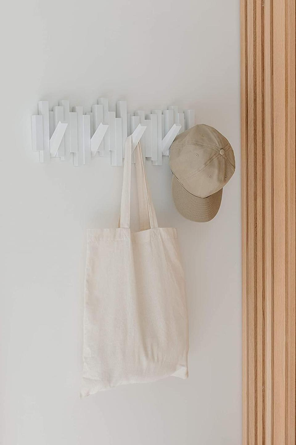 """<h3>Modern Mounted Coat Rack</h3><br>Coat racks are not decor duds — and this $25 sculpturesque piece proves it. <br><br><strong>Umbra</strong> Sticks Modern Mounted Coat Rack, $, available at <a href=""""https://amzn.to/3pXrpm7"""" rel=""""nofollow noopener"""" target=""""_blank"""" data-ylk=""""slk:Amazon"""" class=""""link rapid-noclick-resp"""">Amazon</a>"""