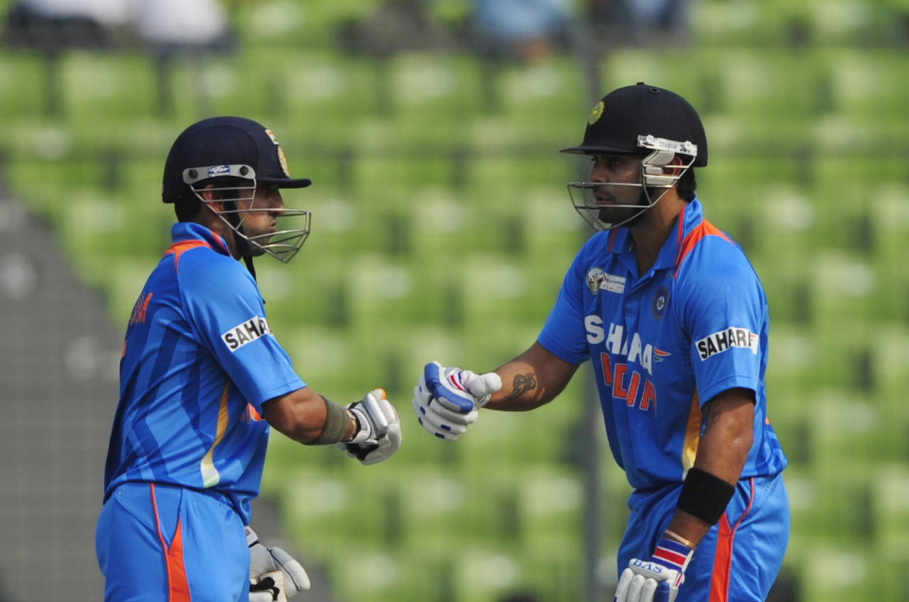 Indian batsman Gautam Gambhir (L) congratulates teammate Virat Kholi for scoring a boundary during the one day international (ODI) Asia Cup cricket match between India and Sri Lanka at The Sher-e-Bangla National Cricket Stadium in Dhaka on March 13, 2012. AFP PHOTO/Munir uz ZAMAN (Photo credit should read MUNIR UZ ZAMAN/AFP/Getty Images)