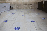 Marks to keep a 2-meter distance are seen on the floor at the Western Wall, the holiest site where Jews can pray in Jerusalem's old city, Wednesday, Sept. 16, 2020. A raging coronavirus outbreak is casting a shadow over the normally festive Jewish New Year. With health officials recommending a nationwide lockdown, traditional family gatherings will be muted, synagogue prayers will be limited to small groups and roads will be empty. (AP Photo/Sebastian Scheiner)
