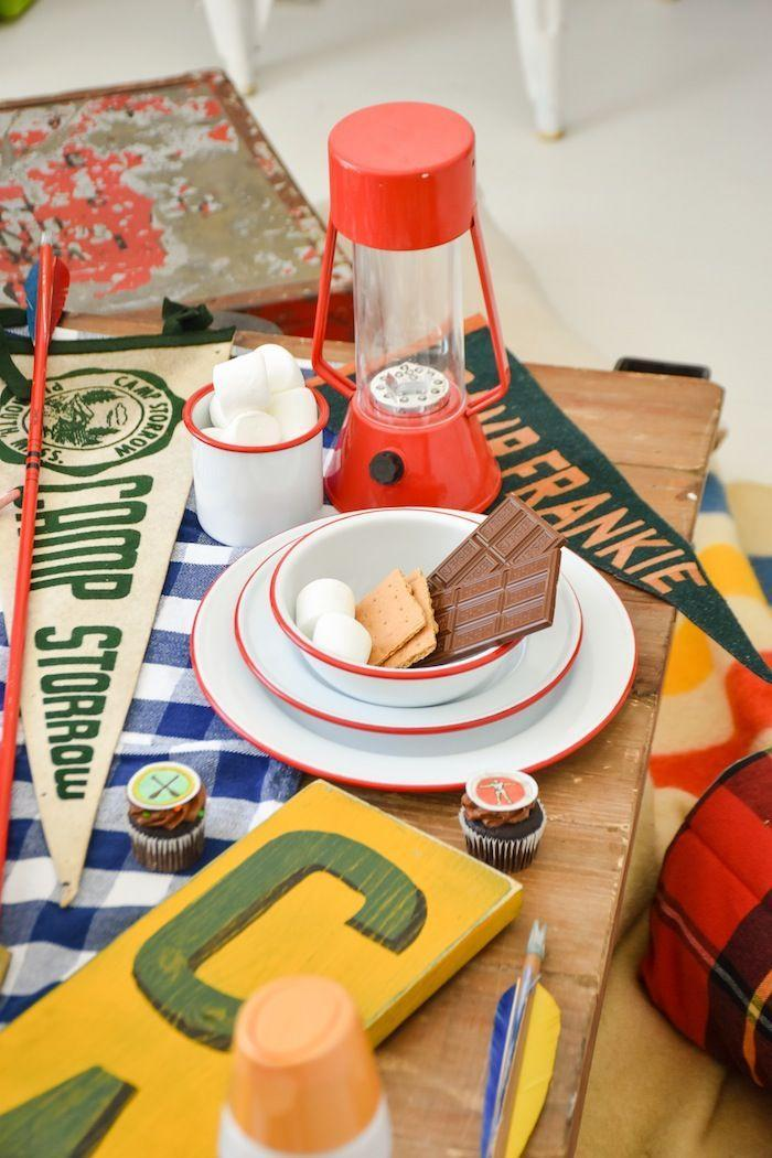 """<p>Throw a summer camp-themed bash in honor of horror flick <em>Friday The 13th. </em>Decor-wise, think vintage lanterns, pennants and plaid blankets. Fill a small wooden boat with ice to house beverages and serve up classic campfire fare, like s'mores and hot dogs. If you really want to go all out, hand out Camp Crystal Lake t-shirts so everyone matches and set up activities, like an archery competition or lawn bowling.</p><p><em>See more of this party at <a href=""""https://karaspartyideas.com/2019/07/summer-camp-party-with-smores-international-delight-creamer.html"""" rel=""""nofollow noopener"""" target=""""_blank"""" data-ylk=""""slk:Kara's Party Ideas"""" class=""""link rapid-noclick-resp"""">Kara's Party Ideas</a>. </em></p><p><a class=""""link rapid-noclick-resp"""" href=""""http://www.amazon.com/dp/B07C2879DP/?tag=syn-yahoo-20&ascsubtag=%5Bartid%7C10072.g.28787574%5Bsrc%7Cyahoo-us"""" rel=""""nofollow noopener"""" target=""""_blank"""" data-ylk=""""slk:SHOP CAMP SHIRTS"""">SHOP CAMP SHIRTS</a></p>"""