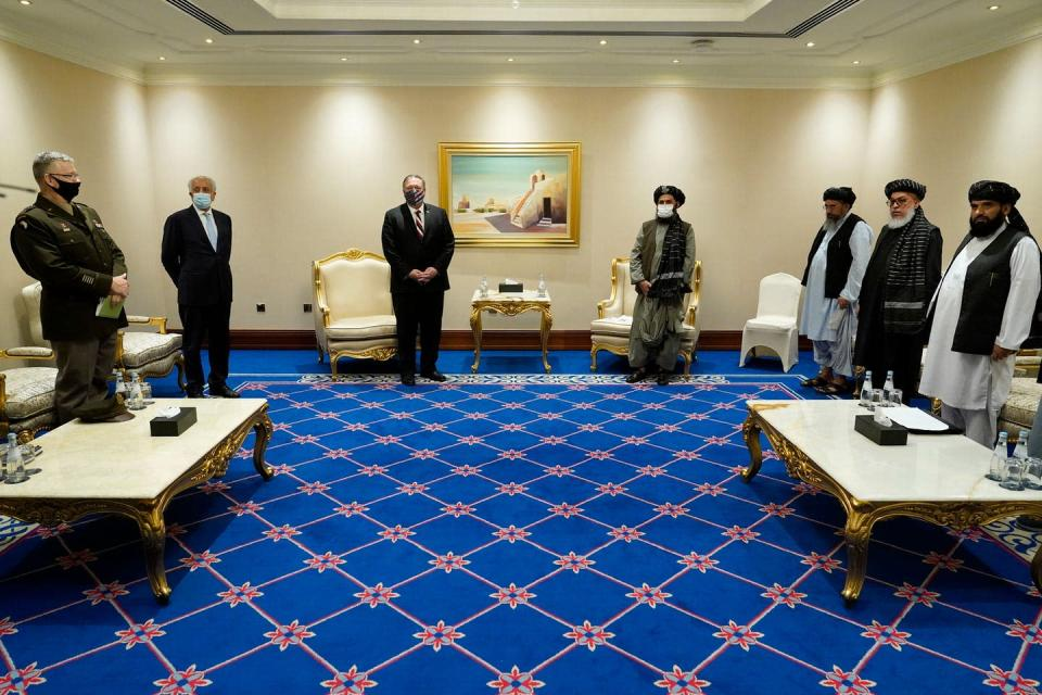 Men, some in suits and other in traditional Pashtun clothing, stand in a hotel conference room at a distance from each other, wearing face masks