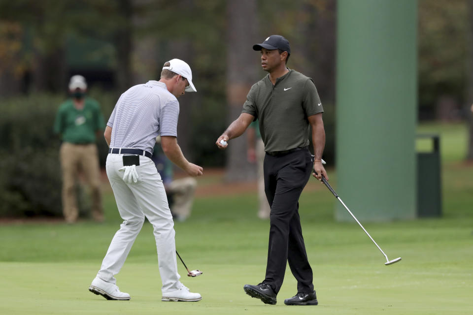 Tiger Woods, right, walks away after a birdie the 15th hole as Andy Ogletree prepares to putt during the first round of the Masters golf tournament Thursday, Nov. 12, 2020, in Augusta, Ga. (Curtis Compton/Atlanta Journal-Constitution via AP)