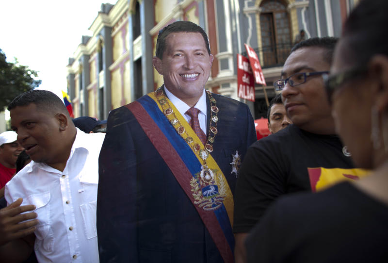 FILE - In this Jan. 10, 2013 file photo, supporters of Venezuela's President Hugo Chavez carry a life-size cut out image of him during a symbolic inauguration ceremony for Chavez, who was in Cuba for cancer treatment at the time, in Caracas, Venezuela. The long and at times surreal saga surrounding the cancer treatment of President Hugo Chavez has many Venezuelan writers and intellectuals likening the nation's drama to a telenovela. Venezuela has long produced soap operas, and some say no one could have imagined a more bizarre plot than the one unfolding in the more than seven weeks since Chavez traveled to Cuba for his operation and disappeared from public view. (AP Photo/Ariana Cubillos, File)