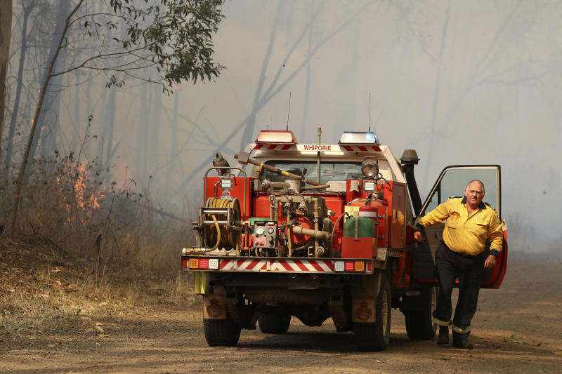 A firefighter gets out of his vehicle near a bushfire burning near Busbys Flat, Australia, Wednesday, Oct. 9, 2019. Parts of Australia's east suffered widespread fire damage with up to 30 homes destroyed as out-of-control wildfires continued to ravage northern New South Wales state. (Jason O'Brien/AAP Image via AP)