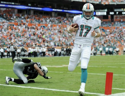 Miami Dolphins quarterback Ryan Tannehill (17) scores a touchdown during the first half of an NFL football game against the Oakland Raiders, Sunday, Sept. 16, 2012, in Miami. (AP Photo/Rhona Wise)