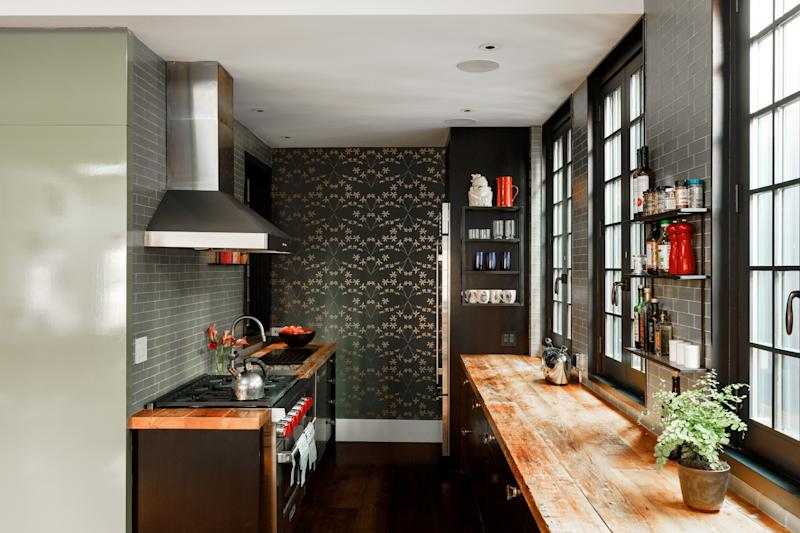 """Among Tierney's many clever design ideas was to repurpose old beams from the house into kitchen countertops. """"You can do anything on them—they're not precious at all,"""" she says. The shelves were custom built by Olde Good Things in New York, and the wallpaper, which extends into the dining area, is Madison and Grow."""