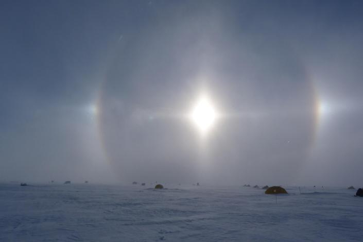 In this Jan. 18, 2013 photo released by scientist Nancy Bertler, a solar halo brightens the sky over the remote camp where Bertler and 13 others worked, on Roosevelt Island, Antarctica. Caused by light reflecting and refracting from ice crystals, such halos are spectacular but typically presage bad weather. Antarctica's pristine habitat provides a laboratory for scientists studying the effects of climate change. (AP Photo/Nancy Bertler)