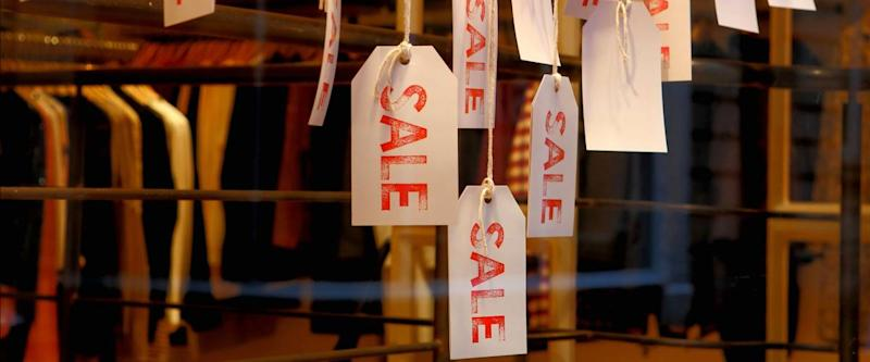 Sale labels hanging in a clothing store as concept of offering products at reduced prices.