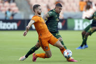 Houston Dynamo defender Adam Lundqvist, left, and Portland Timbers midfielder Marvin Loria, right, battle for the ball during the first half of an MLS soccer match Wednesday, June 23, 2021, in Houston. (AP Photo/Michael Wyke)