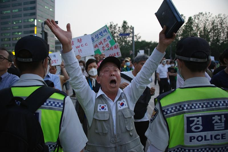 In a photo taken on June 9, 2015 a member of a conservative Christian group holds a bible as he shouts slogans during a protest against the opening ceremony of the 'Queer Korea' gay pride festival in Seoul (AFP Photo/Yelim Lee)