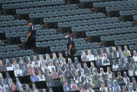 Security personnel walk through the seats and past cardboard cutouts of fane before an opening days baseball game between the Chicago White Sox and the Minnesota Twins, Friday, July 24, 2020, in Chicago. (AP Photo/Charles Rex Arbogast)