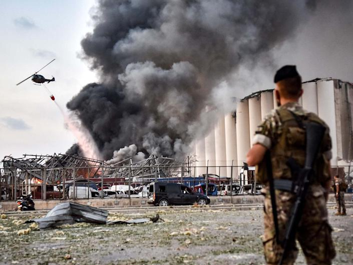 Lebanese army soldiers stand while behind a helicopter puts out a fire at the scene of an explosion at the port of Lebanon's capital Beirut: AFP via Getty Images