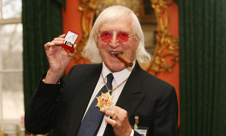 <b>Sir Jimmy Savile (31 October 1926 to 29 July 2011)</b> <br><br>As a renowned DJ, television presenter and charity fundraiser, Sir Jimmy Savile was one of the best-loved British media personalities of the last 50 years. First gaining fame as a DJ and radio host, in 1964 became the inaugural presenter of Top of the Pops. Savile went on to front a series of Public Information Films, including 'Clunk Click Every Trip', and later television series 'Jim'll Fix It'.<br><br>At the height of its popularity, 'Jim'll Fix It' received 20,000 letters a week from children who wanted Savile to make their dreams come true. It was a far cry from his earlier life as a miner, hospital porter, professional wrestler and dance-hall promoter. He also claimed to have been the world's first DJ to join two turntables together to play music continuously.<br><br>Aside from his work on television and radio, Savile was a prolific fundraiser – running more than 200 marathons and bringing in £42million for charities over the years. Savile was known for his eccentricity and fashion sense, frequently clad in tracksuits or shell suits with large gold jewellery. He was also a member of MENSA with an IQ of 149. Savile was found dead at his home in Roundhay, Leeds on 29 November three days before his 85th birthday.