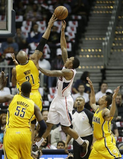 Atlanta Hawks point guard Jeff Teague (0) has his shot blocked by Indiana Pacers power forward David West (21) during the first half of an NBA first-round playoff basketball game in Atlanta, Friday, May 3, 2013. (AP Photo/John Bazemore)