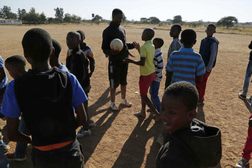 Double amputee and soccer coach, Tebogo Mofokeng, centre, talks with his players prior to a friendly soccer match during a training session in Winterveldt, South Africa, Sunday, June 17, 2018. Mofokeng's legs were amputated when he was a toddler but that didn't stop him fulfilling his dream of coaching young children. (AP Photo/Denis Farrell)