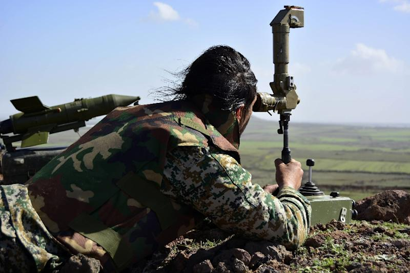 A member of the Syrian government forces looks at enemy positions from the Fatima hill overlooking the town of Kfar Shams, north of the southern Syrian city of Deraa on March 1, 2015, after they regained control of the hill the day before (AFP Photo/)