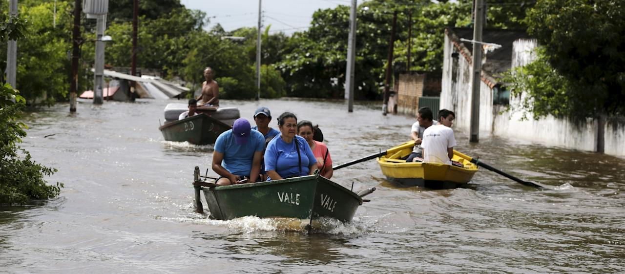 People travel on a boat near flood-affected houses in Asuncion, December 27, 2015. More than 100,000 people have had to evacuate from their homes in the bordering areas of Paraguay, Uruguay, Brazil and Argentina due to severe flooding in the wake of heavy summer rains brought on by El Niño, authorities said on Saturday. REUTERS/Jorge Adorno