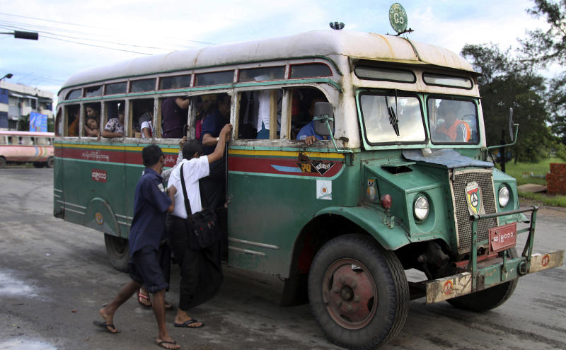 In this Aug. 22, 2012 photo, passengers get into a slowly moving Chevrolet bus in Yangon, Myanmar. These old Chevys built on the Canadian made military personnel carriers that were left behind after World War II were sent to the scrap heap at the end of 2012. Because of the abysmal state of public transport in Yangon, a city of 5 million, those who can afford to drive, do. Those who can't cram into ancient buses perched precariously on huge tires or hitch rides on pickups outfitted with benches and makeshift roofs. (AP Photo/Khin Maung Win)