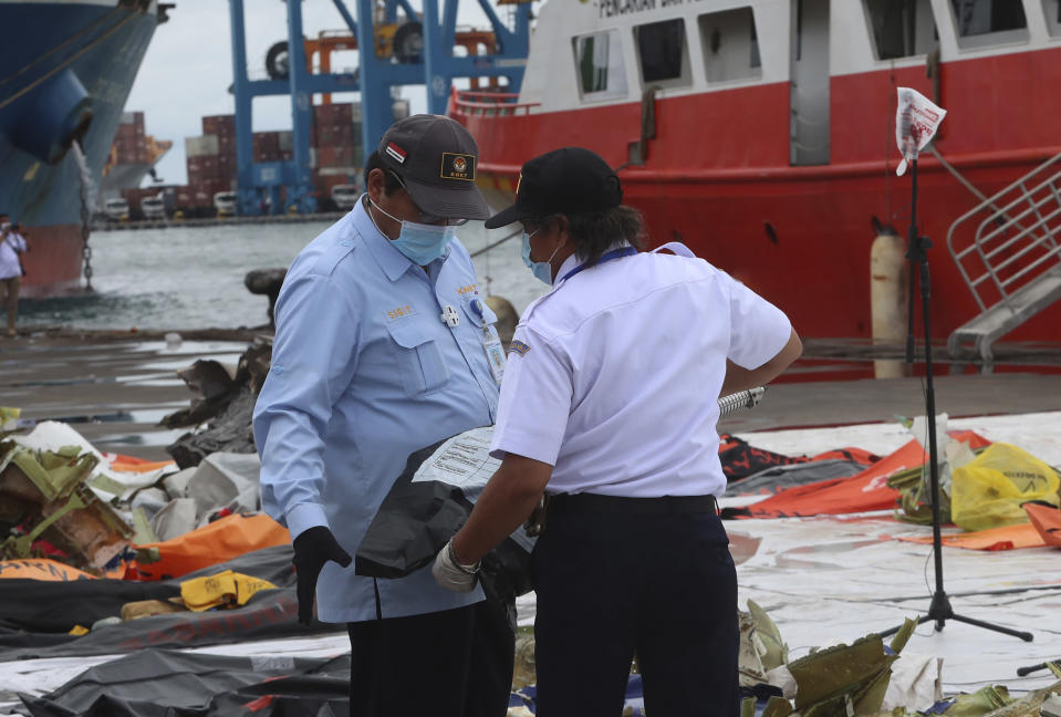 Indonesian National Transportation Safety Committee (KNKT) investigators inspect debris found in the waters around the location where a Sriwijaya Air passenger jet crashed, at the search and rescue command center at Tanjung Priok Port in Jakarta, Indonesia, Indonesia, Wednesday, Jan. 13, 2021. Divers looking for the crashed plane's cockpit voice recorder were searching in mud and plane debris on the seabed between Indonesian islands Wednesday to retrieve information key to learning why the Sriwijaya Air jet nosedived into the water over the weekend. (AP Photo/Achmad Ibrahim)