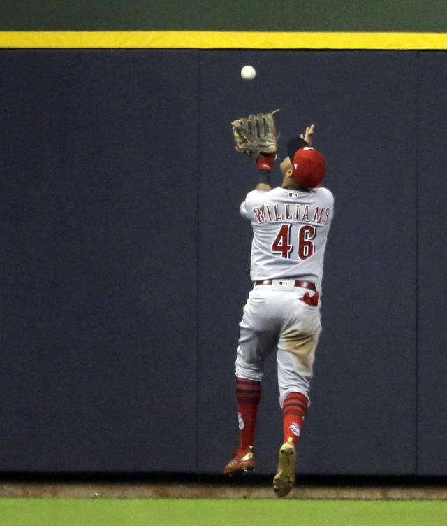 Cincinnati Reds' Mason Williams makes a catch at the wall on a ball hit by Milwaukee Brewers' Curtis Granderson during the sixth inning of a baseball game Tuesday, Sept. 18, 2018, in Milwaukee. (AP Photo/Aaron Gash)